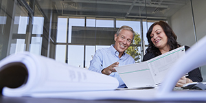 Smiling man and woman reviewing documents at a table.