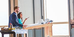 A man and a woman standing at a drafting table in a space under construction pointing out details.