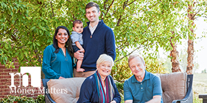 Multiple generation family enjoying day outdoors smiling at camera.