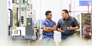 Two men having a conversation as they walk through a manufacturing facility.